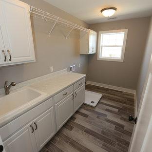 Inredning av en klassisk stor linjär tvättstuga enbart för tvätt, med en nedsänkt diskho, luckor med upphöjd panel, vita skåp, bänkskiva i kvartsit, grå väggar, vinylgolv och en tvättmaskin och torktumlare bredvid varandra