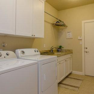 Bild på en mellanstor vintage linjär tvättstuga enbart för tvätt, med en undermonterad diskho, skåp i shakerstil, vita skåp, granitbänkskiva, beige väggar, travertin golv och en tvättmaskin och torktumlare bredvid varandra