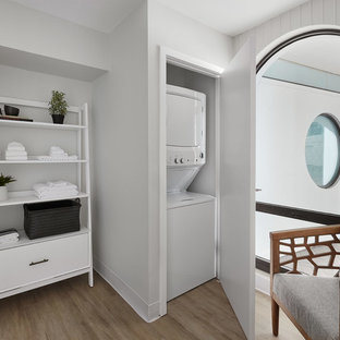 Laundry closet - contemporary light wood floor and beige floor laundry closet idea in Chicago with gray walls and a stacked washer/dryer