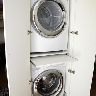 Example of a beach style laundry closet design in Miami with flat-panel cabinets, white cabinets and a stacked washer/dryer