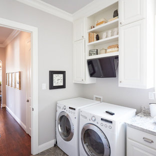 Dedicated laundry room - mid-sized transitional single-wall gray floor and slate floor dedicated laundry room idea in Dallas with gray walls, a side-by-side washer/dryer, raised-panel cabinets, white cabinets and quartzite countertops