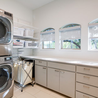 Large contemporary utility room in Dallas with flat-panel cabinets, grey cabinets, white walls, a stacked washer and dryer, composite countertops and vinyl flooring.