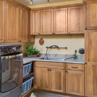 Dedicated laundry room - small craftsman l-shaped concrete floor dedicated laundry room idea in Other with an undermount sink, raised-panel cabinets, medium tone wood cabinets, granite countertops, yellow walls and a side-by-side washer/dryer