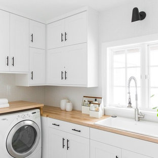 Dedicated laundry room - large transitional l-shaped dedicated laundry room idea in Salt Lake City with shaker cabinets, a drop-in sink, white cabinets, wood countertops, white walls, a side-by-side washer/dryer and beige countertops