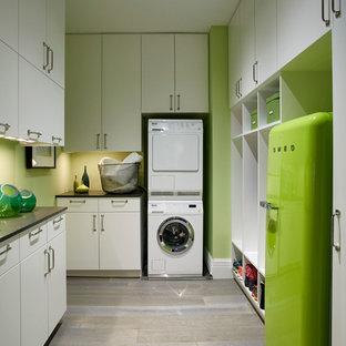 Esempio di una sala lavanderia tradizionale di medie dimensioni con ante lisce, ante bianche, top in quarzo composito, pareti verdi, parquet scuro e lavatrice e asciugatrice a colonna