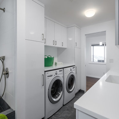Mid-sized trendy galley utility room photo in Portland with flat-panel cabinets, white cabinets, white walls and a side-by-side washer/dryer
