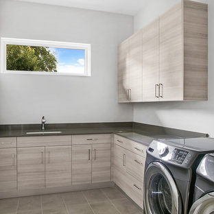 Mid-sized trendy l-shaped beige floor dedicated laundry room photo in Tampa with an undermount sink, flat-panel cabinets, quartz countertops, a side-by-side washer/dryer, gray countertops, gray walls and gray cabinets