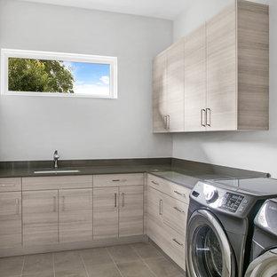 Foto di una sala lavanderia minimal di medie dimensioni con lavello sottopiano, ante lisce, top in quarzo composito, lavatrice e asciugatrice affiancate, top grigio, pareti grigie, pavimento beige e ante grigie