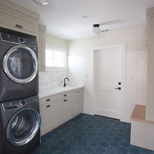 Foto di una lavanderia multiuso country di medie dimensioni con lavello sottopiano, ante in stile shaker, ante grigie, top in quarzite, pareti bianche, pavimento in cemento, lavatrice e asciugatrice a colonna, pavimento blu e top bianco