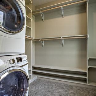 Esempio di una lavanderia multiuso tradizionale di medie dimensioni con ante beige, pareti beige, moquette, lavatrice e asciugatrice a colonna e pavimento beige