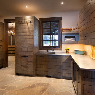 Inspiration for a large rustic u-shaped beige floor laundry room remodel in Seattle with an undermount sink, dark wood cabinets and beige walls