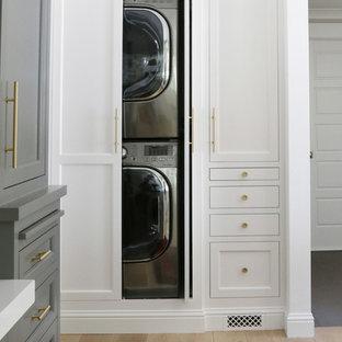 Foto på en liten liten tvättstuga, med vita skåp, vita väggar, ljust trägolv och tvättmaskin och torktumlare byggt in i ett skåp