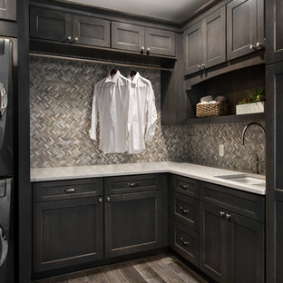 Design ideas for a mid-sized transitional l-shaped laundry room in Detroit with an undermount sink, flat-panel cabinets, dark wood cabinets, quartz benchtops, beige walls, porcelain floors and a stacked washer and dryer.