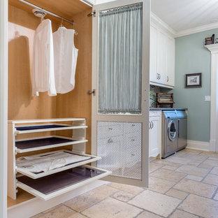 Ispirazione per una sala lavanderia tradizionale di medie dimensioni con ante in stile shaker, ante bianche, pareti blu, lavatrice e asciugatrice affiancate, pavimento in pietra calcarea e pavimento beige