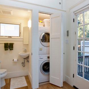 Idées déco pour une petite buanderie linéaire craftsman avec un placard, un évier 1 bac, un placard à porte shaker, un sol en bois brun, des machines superposées, des portes de placard blanches, un mur blanc et un sol marron.