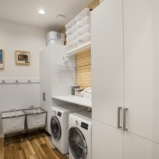 Inspiration for a mid-sized 1950s l-shaped light wood floor and beige floor dedicated laundry room remodel in Dallas with flat-panel cabinets, white cabinets, laminate countertops, white walls and white countertops