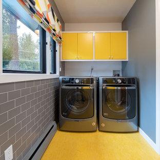 他の地域のミッドセンチュリースタイルのおしゃれな洗濯室 (フラットパネル扉のキャビネット、黄色いキャビネット、グレーの壁、左右配置の洗濯機・乾燥機、黄色い床) の写真