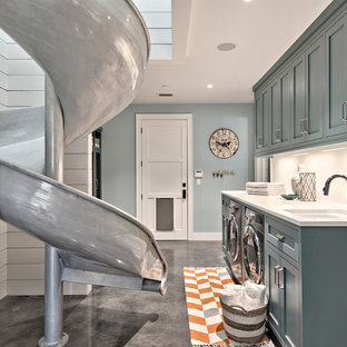 Large farmhouse single-wall separated utility room in Austin with a submerged sink, shaker cabinets, concrete flooring, a side by side washer and dryer, blue cabinets, marble worktops, blue walls, grey floors and white worktops.
