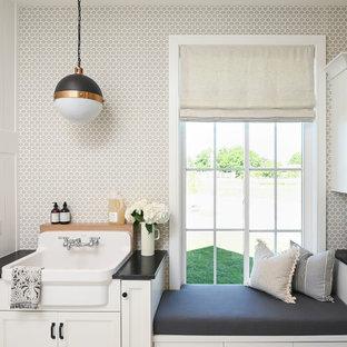 Foto di una lavanderia country con lavello stile country, ante con riquadro incassato, ante bianche, pareti grigie e top nero