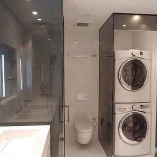Idee per un piccolo ripostiglio-lavanderia con top in vetro, lavatrice e asciugatrice a colonna e pavimento bianco