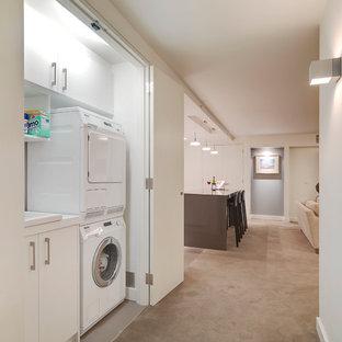 Inspiration för en liten funkis linjär liten tvättstuga, med en nedsänkt diskho, släta luckor, vita skåp, bänkskiva i kvarts, klinkergolv i porslin, tvättmaskin och torktumlare byggt in i ett skåp och vita väggar