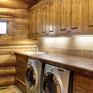 Mid-sized mountain style single-wall slate floor and beige floor dedicated laundry room photo in Seattle with a drop-in sink, raised-panel cabinets, dark wood cabinets, tile countertops, beige walls, a side-by-side washer/dryer and brown countertops