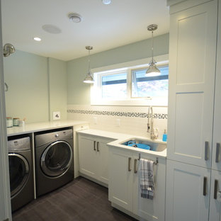 Example of a large transitional l-shaped laundry room design in Vancouver with an undermount sink, shaker cabinets, white cabinets, quartz countertops, gray backsplash and glass tile backsplash