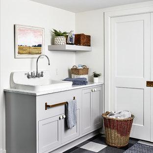 Réalisation d'une buanderie marine avec un placard à porte shaker, des portes de placard grises, un mur blanc, un sol multicolore et un plan de travail blanc.