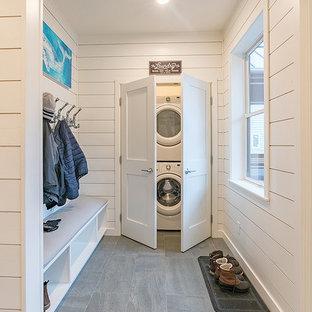 Inspiration pour une buanderie marine de taille moyenne avec un mur blanc, un sol en carrelage de porcelaine, un sol gris, un placard et des machines superposées.