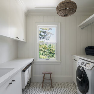 Large contemporary galley separated utility room in San Francisco with a submerged sink, flat-panel cabinets, white cabinets, white walls, white floors, white worktops, marble worktops, ceramic flooring and a side by side washer and dryer.