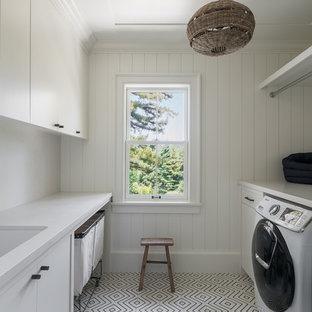 Ispirazione per una grande sala lavanderia minimal con lavello sottopiano, ante lisce, ante bianche, pareti bianche, pavimento bianco, top bianco, top in marmo, pavimento con piastrelle in ceramica e lavatrice e asciugatrice affiancate