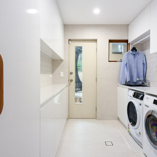 This is an example of a mid-sized modern galley dedicated laundry room in Sydney with a drop-in sink, flat-panel cabinets, white cabinets, quartz benchtops, beige splashback, ceramic splashback, beige walls, ceramic floors, a side-by-side washer and dryer, beige floor and white benchtop.