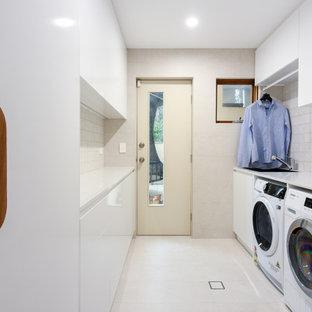 Bild på en mellanstor funkis vita parallell vitt tvättstuga enbart för tvätt, med en nedsänkt diskho, släta luckor, vita skåp, bänkskiva i kvarts, beige stänkskydd, stänkskydd i keramik, beige väggar, klinkergolv i keramik, en tvättmaskin och torktumlare bredvid varandra och beiget golv