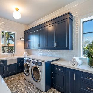 Esempio di una sala lavanderia costiera con lavello stile country, ante con riquadro incassato, ante blu, lavatrice e asciugatrice affiancate, pavimento multicolore e top bianco