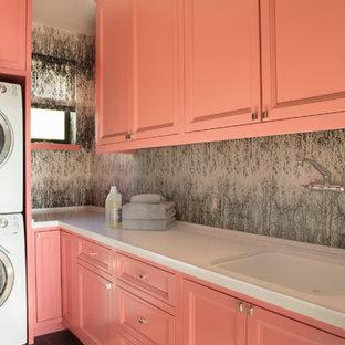 Cette image montre une buanderie bohème en L dédiée et de taille moyenne avec un placard avec porte à panneau encastré, un sol en carrelage de céramique, des portes de placard oranges, un évier encastré et un mur gris.