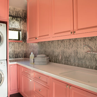 Mid-sized eclectic l-shaped dedicated laundry room in Los Angeles with recessed-panel cabinets, ceramic floors, orange cabinets, an undermount sink and grey walls.