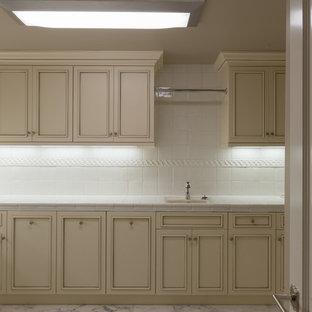 Foto på ett stort funkis u-format grovkök, med en allbänk, luckor med upphöjd panel, vita skåp, kaklad bänkskiva, beige väggar, marmorgolv och en tvättmaskin och torktumlare bredvid varandra