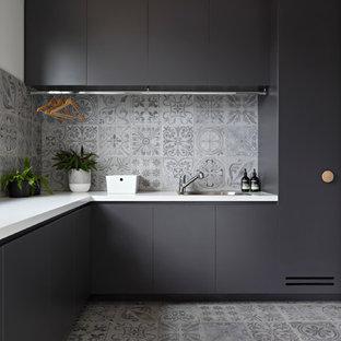 Bild på ett mellanstort funkis l-format grovkök, med klinkergolv i porslin, en undermonterad diskho, släta luckor, svarta skåp, grått golv och vita väggar