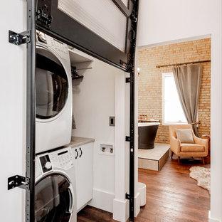 Idéer för att renovera en liten industriell grå linjär grått liten tvättstuga, med släta luckor, vita skåp, laminatbänkskiva, laminatgolv, en tvättpelare, vita väggar och brunt golv