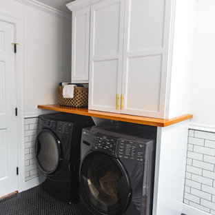 Photo of a mid-sized transitional galley utility room in Boston with shaker cabinets, white cabinets, wood benchtops, white walls, ceramic floors, a side-by-side washer and dryer and black floor.