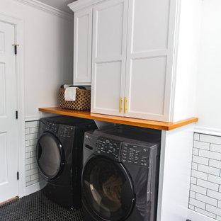 Klassisk inredning av ett mellanstort parallellt grovkök, med skåp i shakerstil, vita skåp, träbänkskiva, vita väggar, klinkergolv i keramik, en tvättmaskin och torktumlare bredvid varandra och svart golv