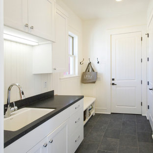 Medium sized farmhouse single-wall utility room in San Francisco with a submerged sink, shaker cabinets, white cabinets, composite countertops, white walls, slate flooring and black worktops.