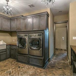 Esempio di una grande sala lavanderia stile rurale con lavello stile country, ante con riquadro incassato, ante grigie, top in legno, pareti beige, pavimento in mattoni e lavatrice e asciugatrice affiancate
