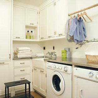 Exempel på en klassisk tvättstuga, med en rustik diskho, bänkskiva i rostfritt stål och vita skåp