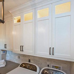 Exemple d'une buanderie linéaire romantique dédiée et de taille moyenne avec un placard à porte shaker, des portes de placard blanches, un plan de travail en quartz modifié, un mur gris, un sol en carrelage de porcelaine, des machines côte à côte et un sol marron.