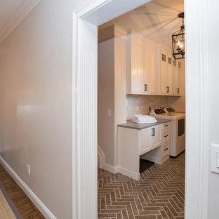 Idee per una sala lavanderia stile shabby di medie dimensioni con ante in stile shaker, ante bianche, top in quarzo composito, pareti grigie, pavimento in gres porcellanato, lavatrice e asciugatrice affiancate e pavimento marrone