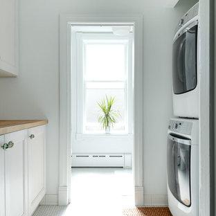 Inspiration för en mellanstor vintage bruna parallell brunt tvättstuga enbart för tvätt, med luckor med infälld panel, vita skåp, träbänkskiva, vita väggar, klinkergolv i porslin, en tvättpelare och vitt golv
