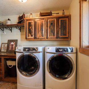 Esempio di una sala lavanderia rustica di medie dimensioni con ante con bugna sagomata, ante con finitura invecchiata, pareti bianche e lavatrice e asciugatrice affiancate
