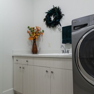 Design ideas for a mid-sized contemporary galley dedicated laundry room in Other with a drop-in sink, flat-panel cabinets, light wood cabinets, terrazzo benchtops, white walls, ceramic floors, a side-by-side washer and dryer and beige floor.