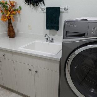 Ispirazione per una sala lavanderia design di medie dimensioni con lavello da incasso, pareti bianche, pavimento con piastrelle in ceramica, pavimento beige, ante lisce, ante in legno chiaro, top alla veneziana e lavatrice e asciugatrice affiancate